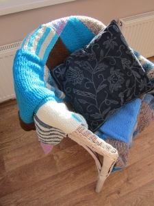 Patchwork blanket and recently dyed cushion cover on revamped wicker chair