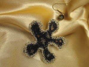 Lacy earring created by freehand machine-stitching on vanishing fabric.